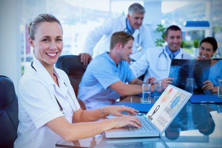 Mooie glimlachende arts die op toetsenbord met haar team erachter tegen menselijk skelet met diverse medische informatie typen Stockfoto