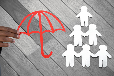 underwriter: hand holding a red umbrella against paper cut out figures forming human pyramid