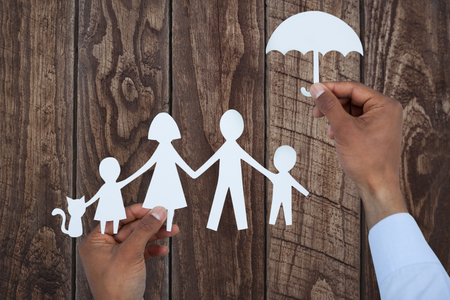hand holding an umbrella and a family in paper against wood panelling