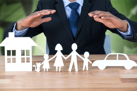 underwriter: underwriter protecting family in paper with his hands against office buildings with graphs Stock Photo