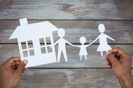 underwriter: hands holding a family with her house in paper against wood Stock Photo