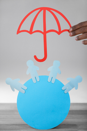 hand holding a red umbrella against blue paper cut out figures on circle Imagens