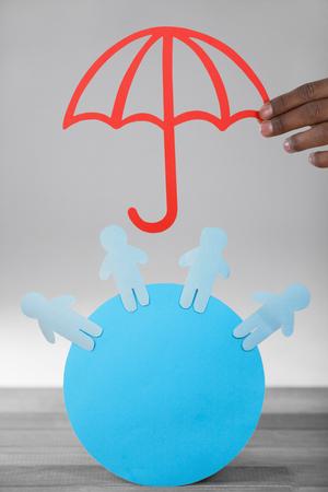 hand met een rode paraplu tegen blauw papier uitgesneden cijfers over cirkel