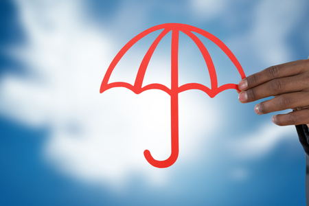 underwriter: hand holding a red umbrella against blue sky with clouds Stock Photo