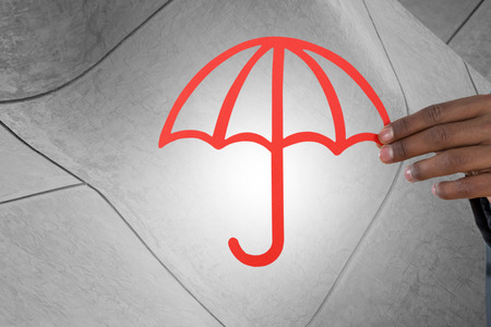 underwriter: hand holding a red umbrella against view of building exterior