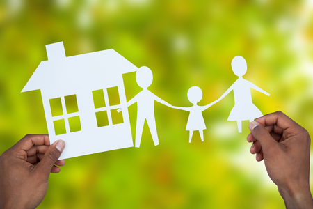 underwriter: hands holding a family with her house in paper against detail shot of bright green leaves Stock Photo