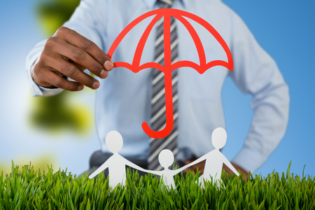 insurer: family protected by a red umbrella against trees against clear blue sky on sunny day