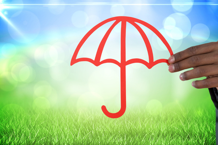 underwriter: hand holding a red umbrella against grass under a sunny sky