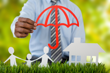 insurer: insurer protecting family by a red umbrella against detail shot of bright green leaves