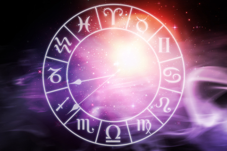 Digitally composite image of clock with various Zodiac signs  against digitally composite image of colorful lights Stock Photo