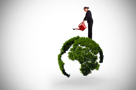 Businesswoman using red watering can against earth outline made of leaves