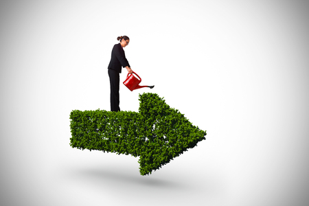Businesswoman using red watering can against arrow made of leaves Stock Photo