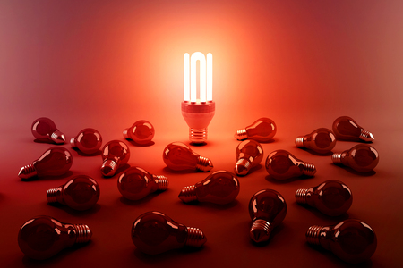 Digital composite image of illuminated energy efficient lightbulb by bulbs on gray background