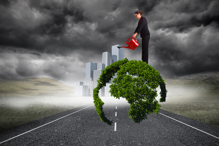 Businesswoman using red watering can against cityscape on stormy landscape background Stock Photo