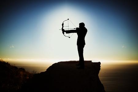 Silhouetzakenman die doel met boog en pijl nemen tegen toneelmening van berg door overzees tegen hemel