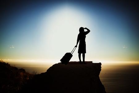 Silhouetonderneemster met koffer tegen toneelmening van berg door overzees tegen hemel