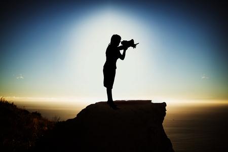 De holdingsmegafoon van de silhouetonderneemster tegen toneelmening van berg door overzees tegen hemel