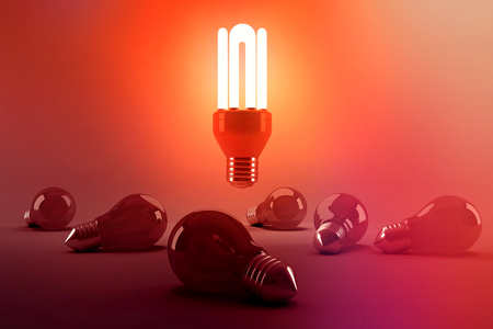 Digitally generated image of illuminated energy efficient lightbulb over bulbs on gray background