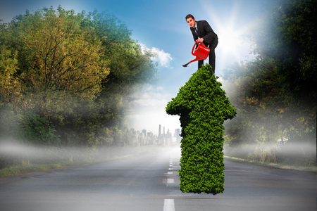 Businessman watering with red can against open road Stock Photo
