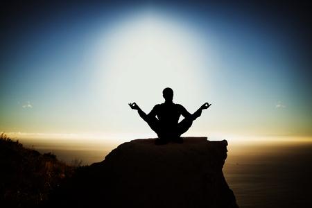 Silhouet zakenman oefenen yoga tegen schilderachtig uitzicht op de berg tegen zee tegen de hemel