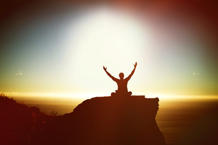 hand on chin: Silhouette businessman with arms raised  against scenic view of mountain by sea against sky Stock Photo
