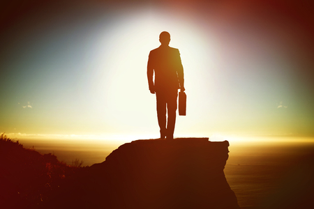 Silhouette man holding briefcase while walking against scenic view of mountain by sea against sky Stock Photo