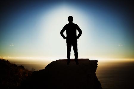 Silhouetzakenman met hand op heup tegen toneelmening van berg door overzees tegen hemel