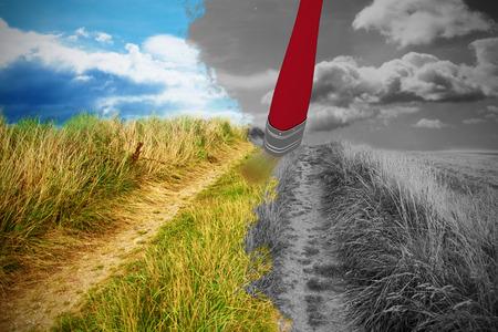 Digital composite image of red paintbrush against blue sky over sand dunes