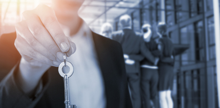 Mid section of businesswoman showing house key against businesspeople forming huddle in office premises Stock Photo