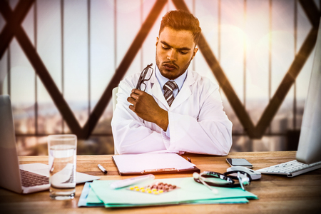 Doctor looking medical report at desk against aerial view of new york