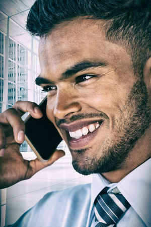 Smiling businessman talking on mobile phone against modern room overlooking city