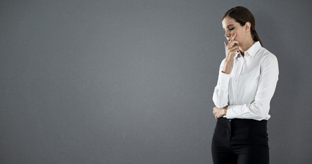 Thoughtful businesswoman standing with hand on face against grey background Stock Photo