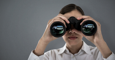 Close up of businesswoman looking through binoculars against grey background