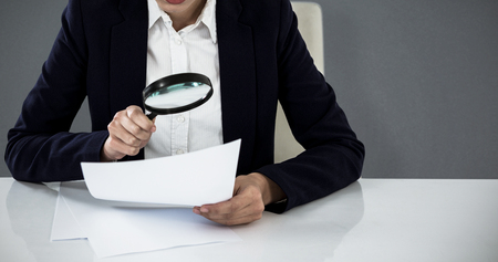 Businesswoman looking at document through magnifying glass against grey background