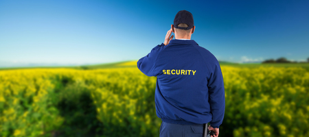 earpiece: Rear view of security officer listening to earpiece against yellow mustard field