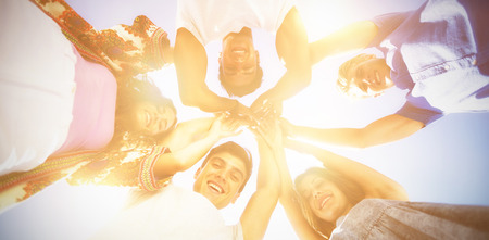 Directly below shot of friends huddling with arms raised against sky on sunny day Standard-Bild