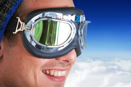 quadratic: Close up of smiling man wearing aviator goggles against blue sky over clouds