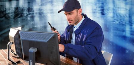 Focused security officer looking observing computer monitors and talking on walkie talkie against virus background 写真素材