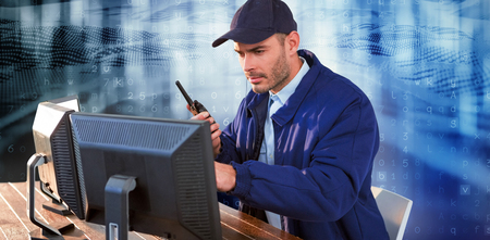 Focused security officer looking observing computer monitors and talking on walkie talkie against virus background Stockfoto