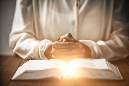 Bright spot of a flare against mid section of woman sitting at desk by bible Stock Photo