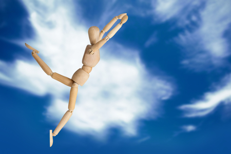 Wooden 3d figurine exercising against blue sky with clouds