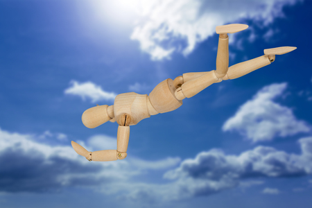 Figurine 3d performing headstand against blue sky
