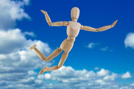 Illustrazione 3d della figurina di legno spensierata che salta in aria contro la vista scenica di cielo blu