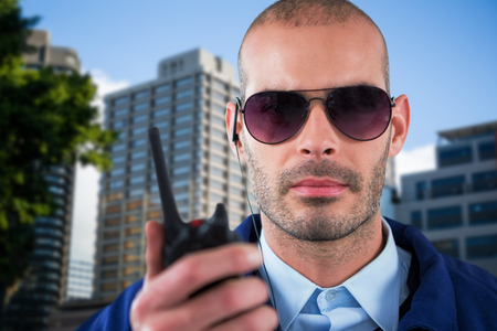 earpiece: Portrait of security officer talking on walkie talkie against beautiful cityscape against clear sky