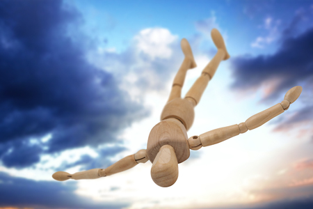 Wooden 3d figurine lying on floor with arms spread against cloudy sky Stock Photo