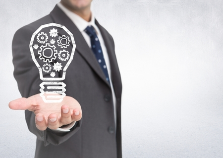booked: Digital composite of Business man hand out with lightbulb doodle against white wall Stock Photo