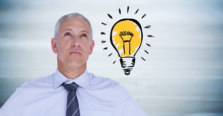 Digital composite of Business man thinking with lightbulb doodle against blurry blue wood panel Stock Photo