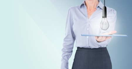 using tablet: Digital composite of Business woman mid section with lightbulb doodles on tablet against blue background