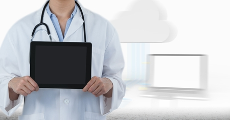 doctor tablet: Digital composite of Doctor mid section with tablet against blurry screens