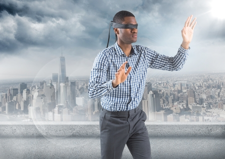 Digital composite of Business man blindfolded with flare against skyline and grey clouds